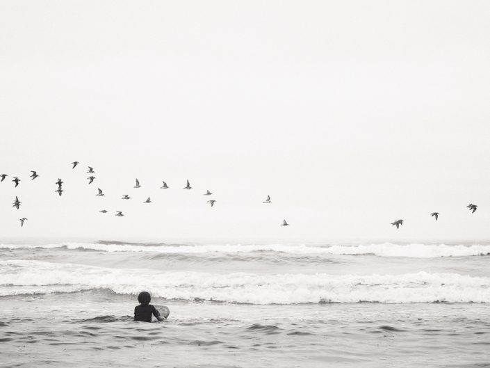 boy in ocean waves at the beach with birds flying in the sky