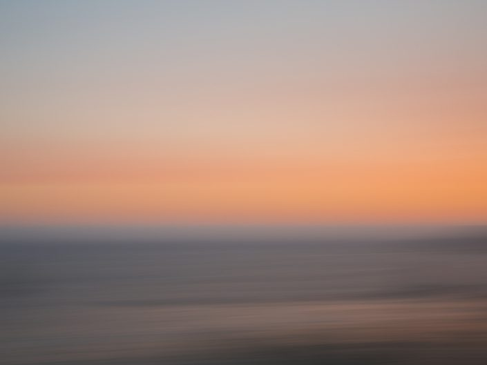 panning abstract of the coastline water and sky at sunset